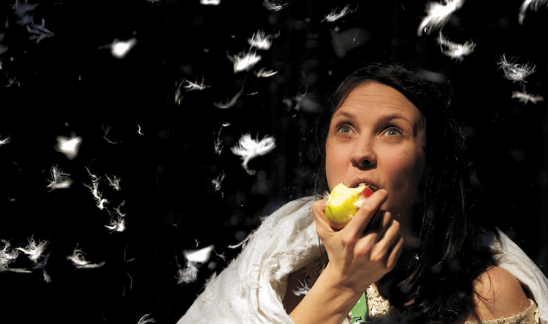 A woman eating an apple, as she watches white feathers fall down around her.