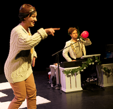 A woman pointing the audience; a man behind her is sitting at a keyboard blowing up a balloon.