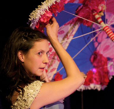 A woman looking back over her shoulder, standing slightly under a parasol.