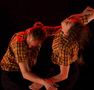 A man and woman dancing, one leans forward, the other leans back, their arms touching and overlapping.