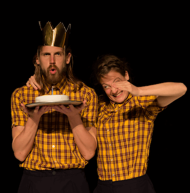 A man blowing out one candle on a cake, wearing a crown party hat. The woman stands next to him with her hand positioned towards the cake.