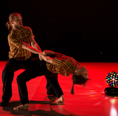 A man and woman dancing, the woman leans backwards holding onto the man's arms, there is a disco ball to the side of them.
