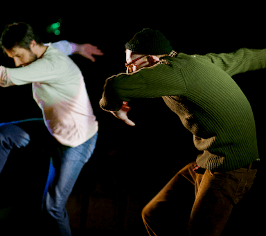 Two men dancing, with their arms out in front and behind them, bending one knee up.