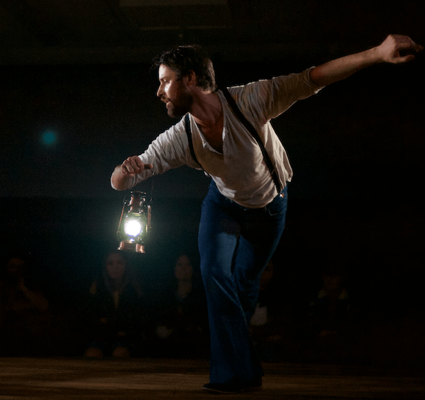 A man cross his legs, while slightly bent over holding a lantern with his other arm stretched out.