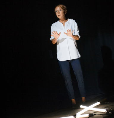 A woman in a white blouse and cropped trousers, she holds her hands out in front of her. Three light tubes lay on the floor crossing over one another.