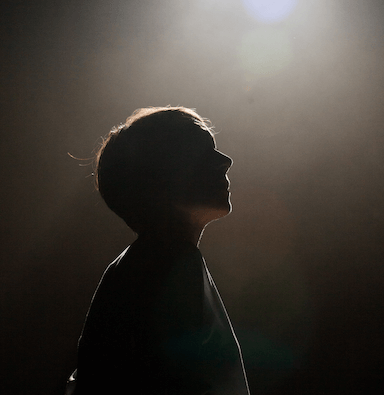 The silhouette of a woman with a light above her head.