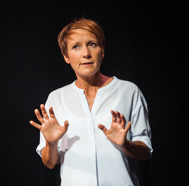 A woman in a white blouse with both her hands up in front of her, not looking directly at the camera