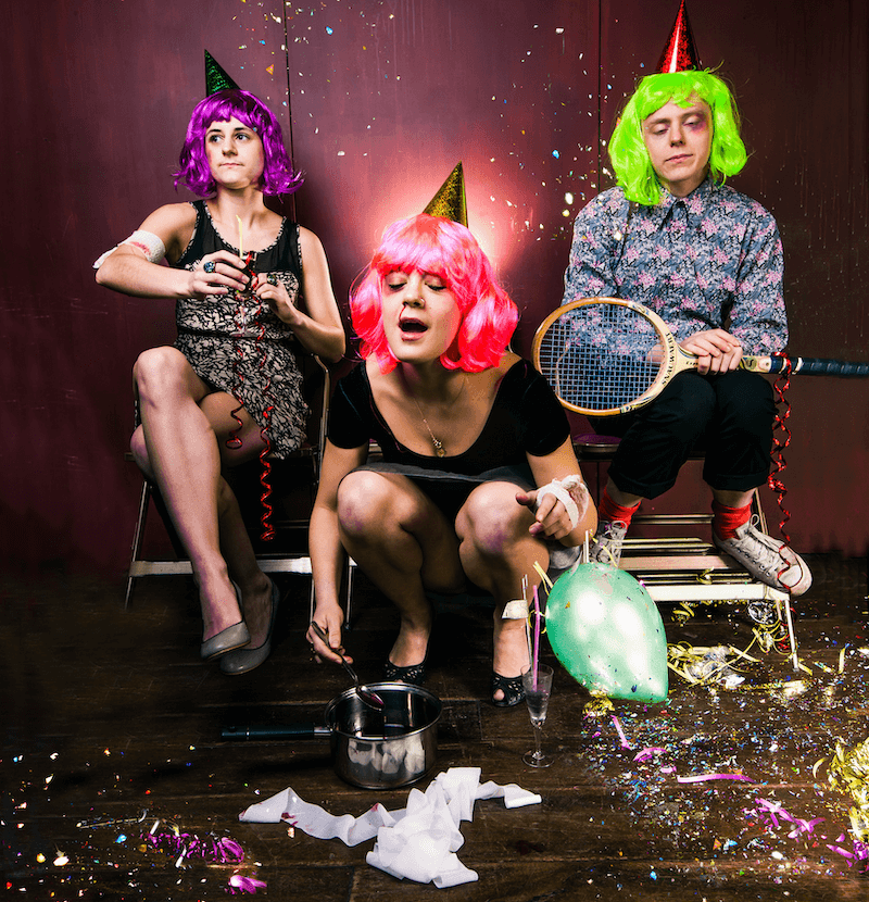 Two women and a man, dressed in bright wigs, party hats and going out outfits, two of them are sat on chairs, the woman in the middle crouches over a saucepan.