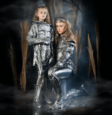 A young child and woman dressed in silver armour, the woman is knelt down next to the young child.
