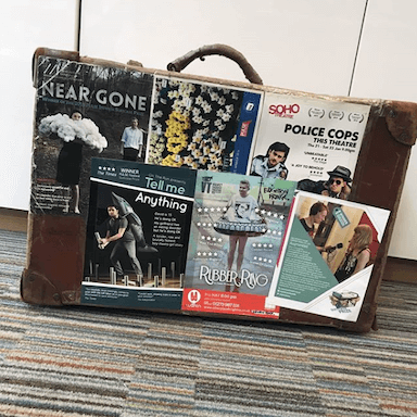 A brown suitcase covered in theatre flyers.