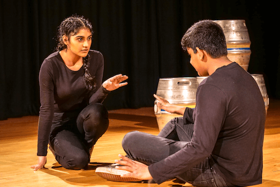 Two students performing on stage, knelt and sat down facing one another, with 3 kegs behind them.