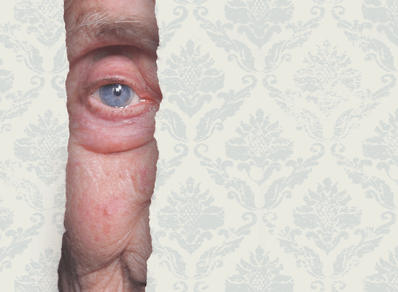 An image of an elderly person eye appearing through a ripped wallpaper panel.