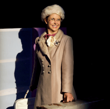 A woman looking to the audience under a spotlight, she is holding two suitcases and wears a brown coat, beret and glasses.