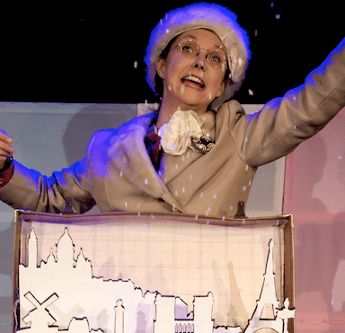 A woman throwing confetti, part of a suitcase is visible.