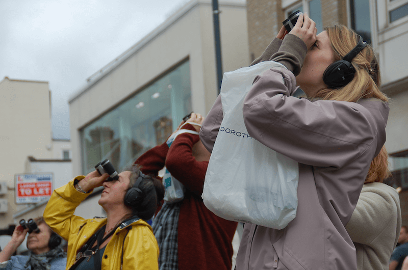 A group of people wearing headphones looking up towards the sky with binoculars on the street.