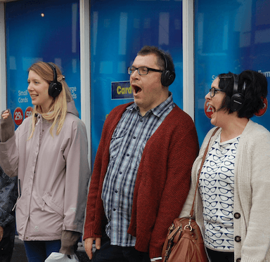 Three people stand in front of a shop window, wearing headphones, their expressions are shocked and surprised.