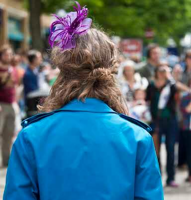 A woman stands with her back to the camera, she is wearing a blue coat and purple flower in her hair.