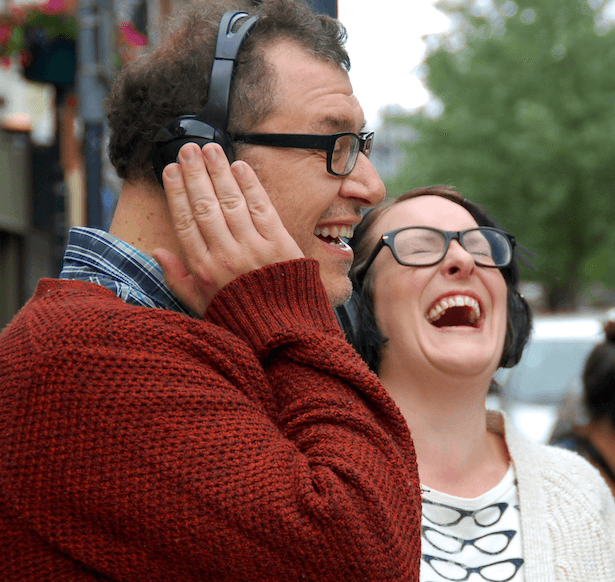 A man wearing headphones is listening and laughing, another woman by him is also wearing headphones and laughing.