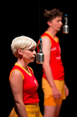A young woman standing in front of a hanging microphone, behind her another man is doing the same.