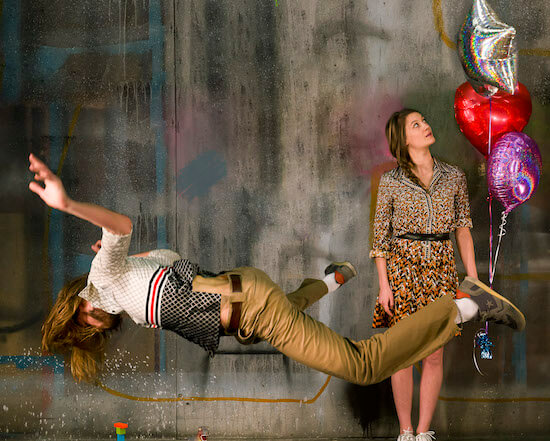 A man levitating in the air face down, a woman stands behind him holding three helium balloons.