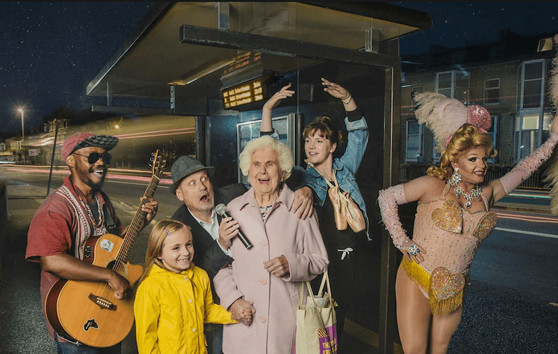A group of people standing by a bus stop, one man has a guitar, another holds a microphone, an elderly lady is laughing, a young woman has ballet shoes round her neck, another person is dressed in drag.