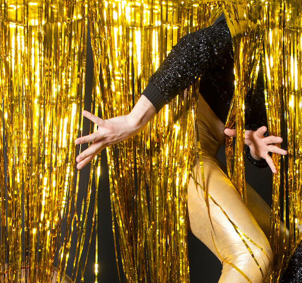 An image of a person sticking their arms and legs through some hanging gold streamers.