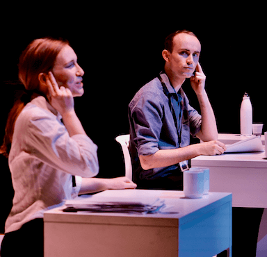 A young woman sits at a desk, appearing to speak to someone on the phone, a young man looks towards her from his desk.