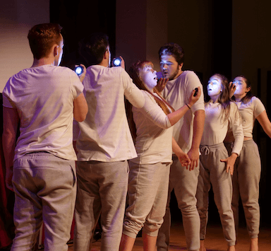 A group of young people lined up one behind the other, all wearing white tops and grey trousers, they each hold a hand touch to their face.