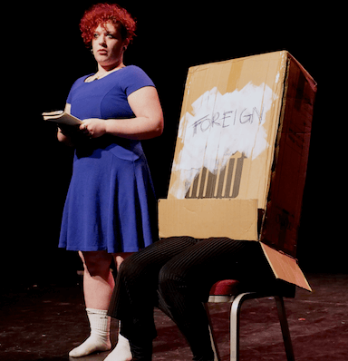 A person in a blue dress looks towards the audience, reading from a notebook, next to them is another person sitting on a chair under a cardboard box which reads 'Foreign'