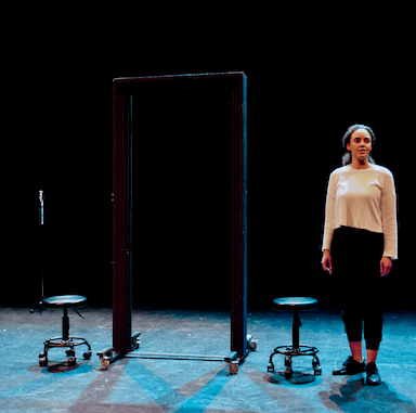 A young woman standing on stage looking to the audience, to her right is a door frame on wheels and two small stools on wheels.