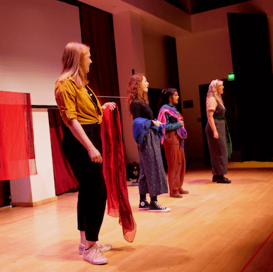 Four young women standing side by side, looking out to the audience.