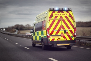 An image of the back of an ambulance driving on a motorway, with its lights flashing.