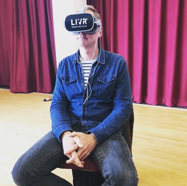 A man sits on a chair wearing a LIVR virtual headset.