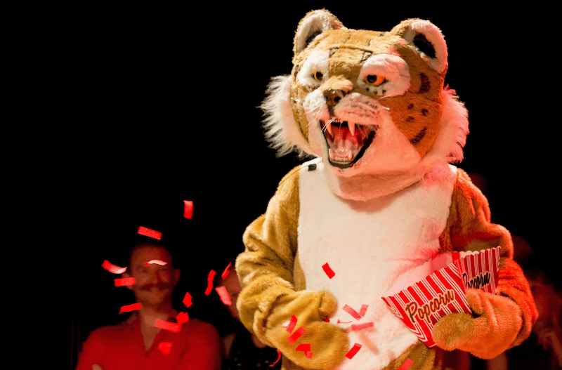 A person dressed up as a tiger mascot holding a popcorn box, chucking red confetti.