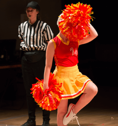 A young woman cheerleading with two pompoms, behind her a referee stands with a whistle in their mouth.