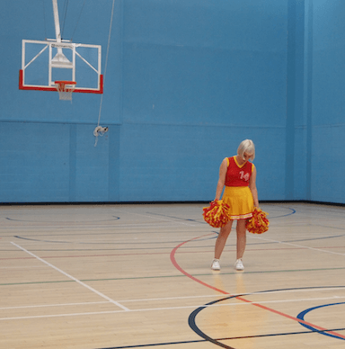 A young woman standing in a gym looking down to the floor holding two pompoms, dressed as a cheer leader.