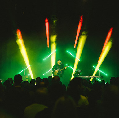 A crowd watching a man playing a guitar and singing into a microphone on stage, with yellow, green and red lights behind him.