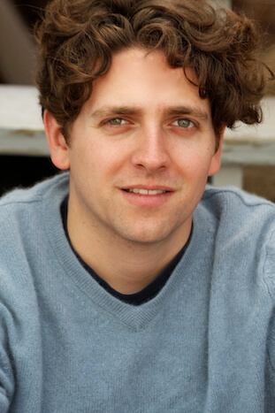 A man with curly brown hair looking directly at the camera, wearing a blue jumper.