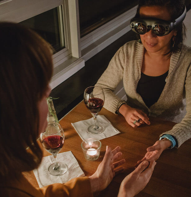 Two women face one another across a table, which has two glasses of wine on it. The woman facing the camera is wearing some goggles, she holds her hand out to the other woman.
