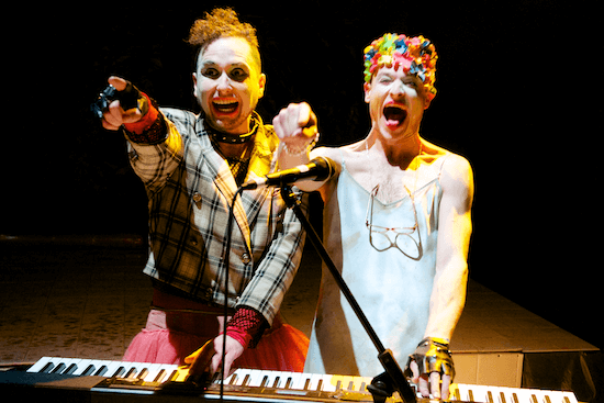 Two people standing at a keyboard, laughing and pointing out towards the camera.