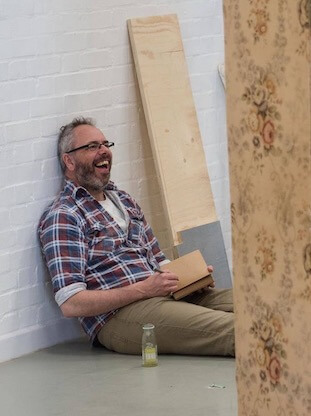 A man sitting on the floor, leaning against a white brick wall, holding a notebook. He appears to be laughing at something out of view of the camera.