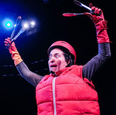 A woman dressed in a red body warmer, helmet and gloves, has her arms raised waving around spatulas.
