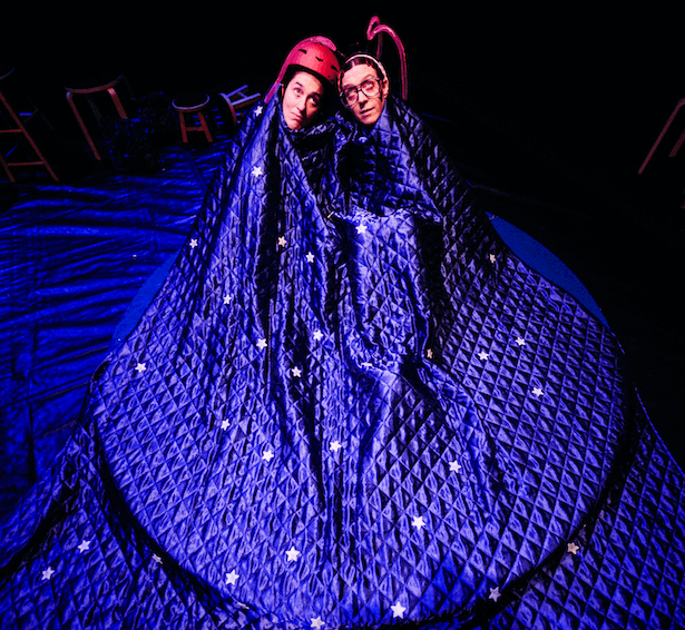 Two people sit under a purple cloak looking upwards.
