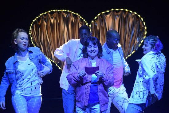 A group of people dancing under a UV light, the woman at the front is reading from a piece of paper, a heart of lights can be seen behind them.