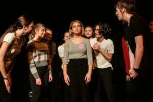 A group of young people performing in a semi-circle.