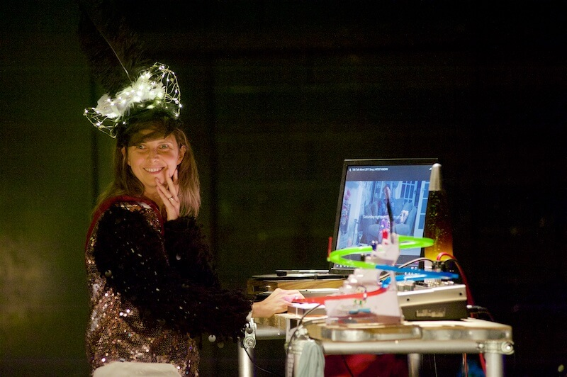 A woman wearing a head dress, standing at a table made of scaffolding, which has a computer screen on top of it.
