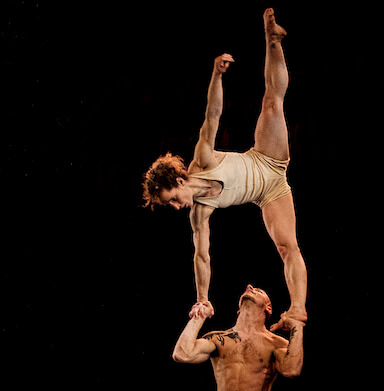 A man holding a woman up in the air, she balances on his hands in the splits position