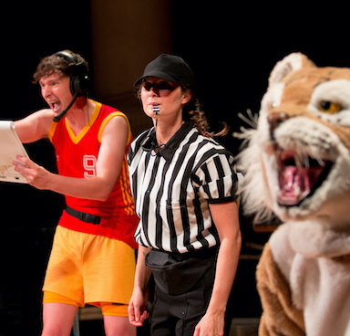 A young woman referee blowing a whistle, behind her a man is shouting orders holding a clip board, in front of her you can see a tiger mascot.