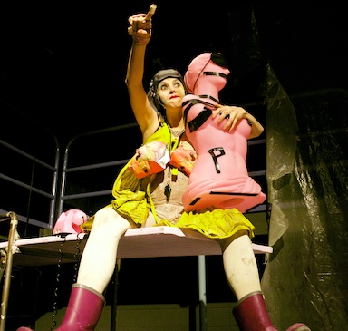 A woman sitting on a ledge, holding a pink mannequin, pointing to something out of shot.