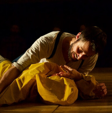 A man lying down with another individual wearing a yellow coat.